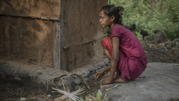 A 16-year old female from Nepal outside a shed where she must sleep