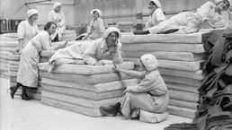 Female workers lie on the asbestos mattresses they have produced at a Lancashire factory. 1914.