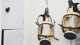 Phantom full-face masks for asbestos removal, hanging in the clean end of the decontamination unit.