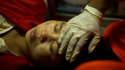 Ambulance attendant Zaw Sai from the Free Funeral Service Society in Yangon comforts a pregnant woman en route to a hospital.