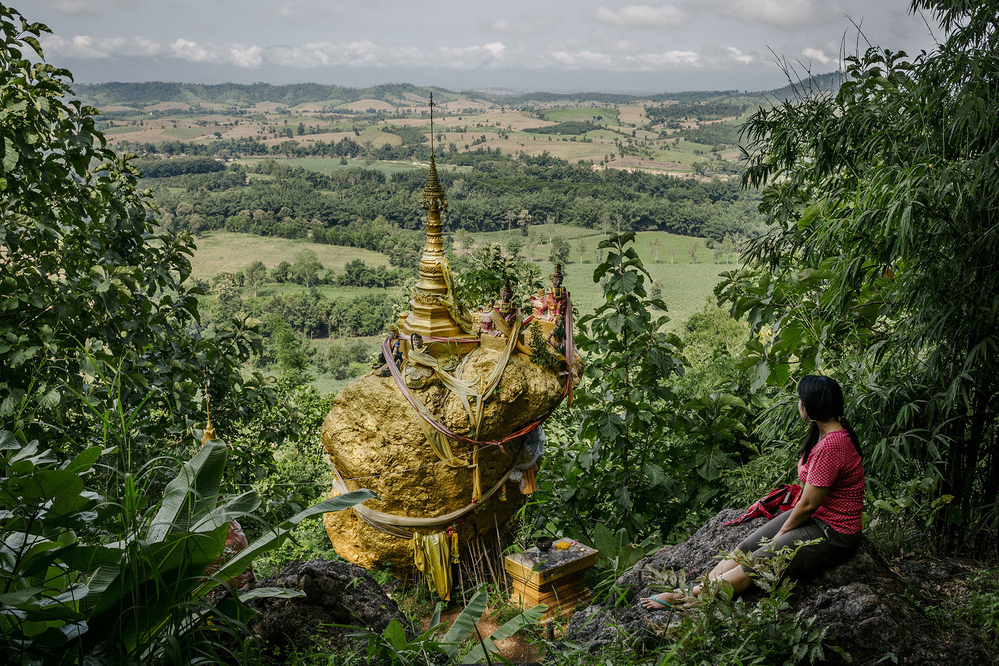 A Buddhist shrine on a rock covered with gold leaves, overlooking the border with Myanmar.