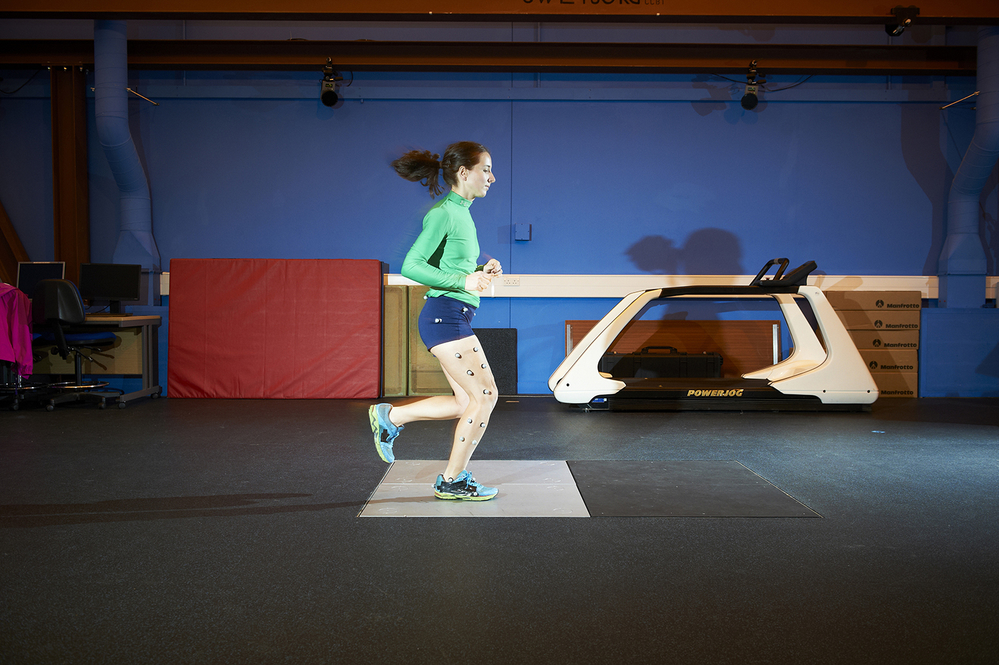 A female runner running across a foot plate in a biomechanic lab