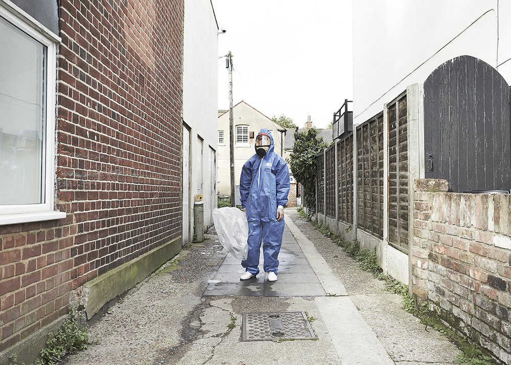 An asbestos removal operative stands in blue transit overalls outside a building.