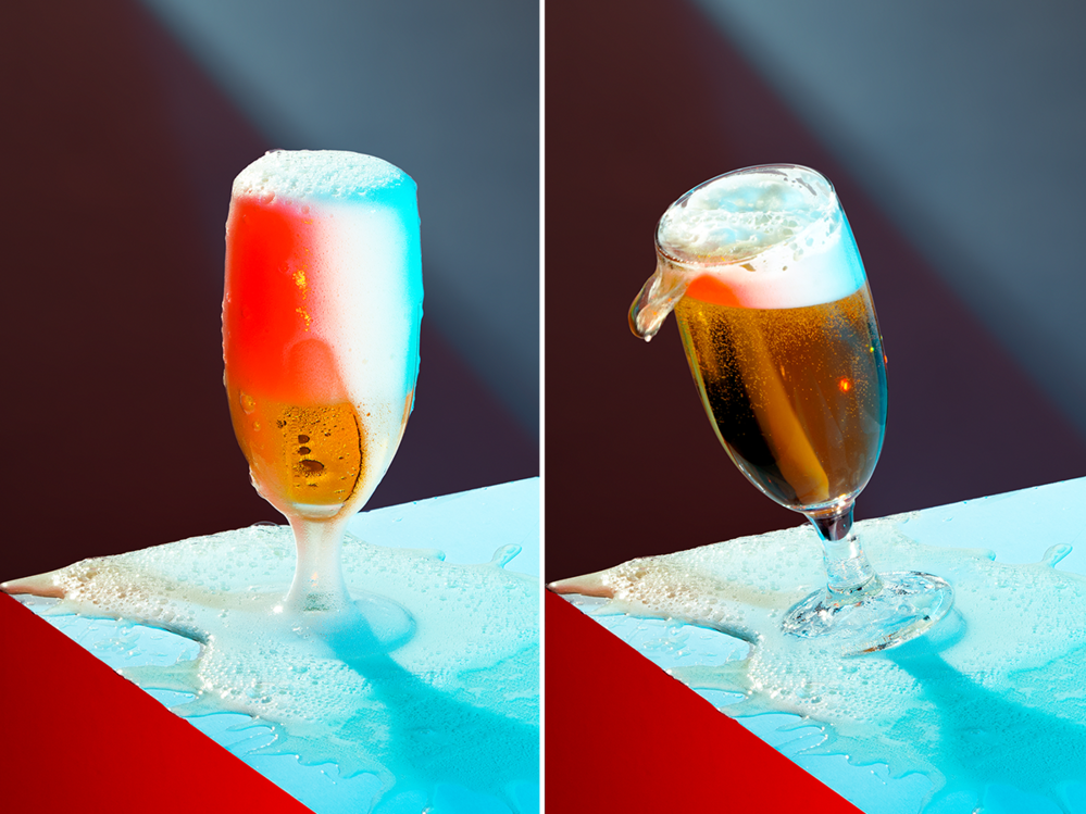 A photograph of a glass of beer foaming and tilting