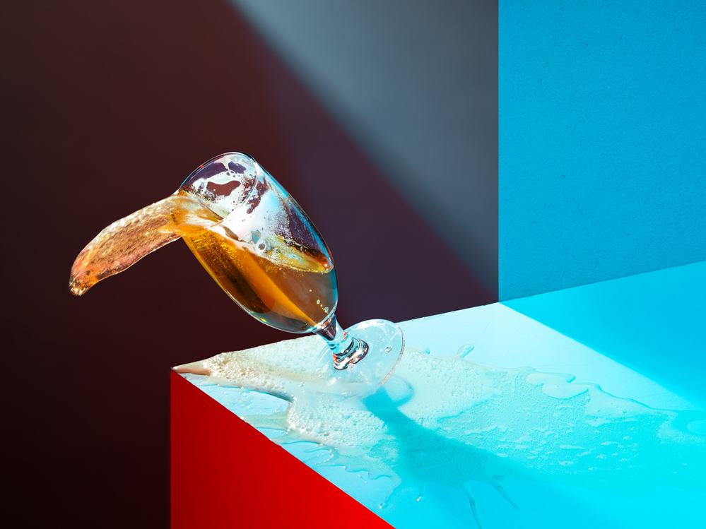A photograph of a glass of beer toppling over