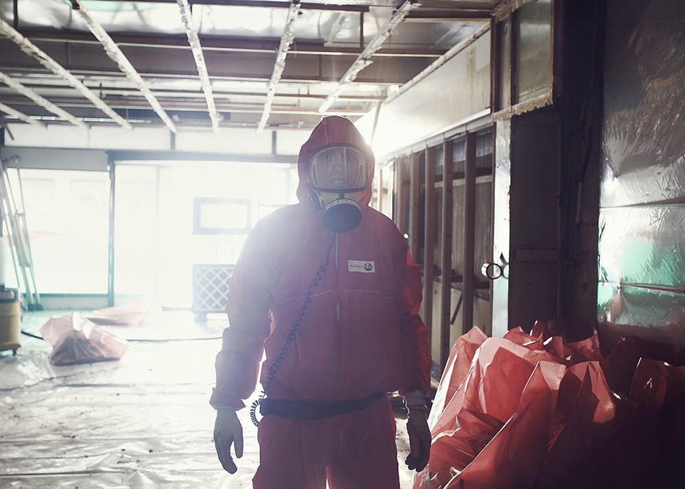 An asbestos operative preparing to seal the asbestos waste bags, ready for removal.